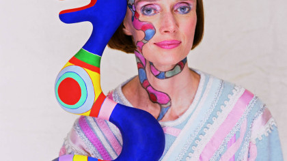 Niki de Saint Phalle holds a snake sculpture while wearing a face painting of a snake. --- Image by © Norman Parkinson/Corbis